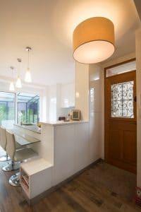 Delimitada por una barra muy práctica, esta cocina abierta al hall de entrada rezuma modernidad.  Una cocina blanca brillante que no carece de estilo para una decoración moderna.