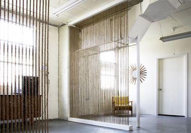 Una solución original para separar la zona de entrada de la casa y la oficina con cuerdas que permiten mantener toda la luminosidad de la estancia.