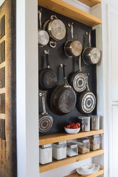 Aquí tienes un consejo para guardar ollas y frascos en una cocina que carece de alacenas.  En un hueco, ollas y jarras encuentran su lugar en los estantes de teca.