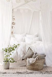 Esta acogedora habitación blanca con cortinas, parquet encalado y alfombra beige se apropia de un ambiente suave donde las cortinas hacen un dosel de la cama para un capullo encantador
