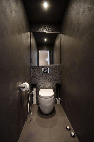 Inodoro de diseño Deco con paredes de estuco gris topo, cuenco colgante blanco de papel gris metalizado, en el suelo un color gris topo