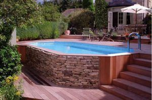 Dispuesta debajo de la terraza de madera, esta encantadora piscina sobre el suelo con piedra y madera en un estilo auténtico realzará su decoración al aire libre.
