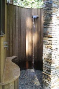 Una ducha de jardín instalada en un patio construido en redondeado con tablones de teca y un pilar de piedra para completar el redondeo.