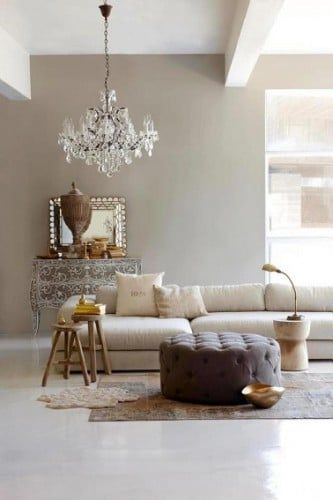 Este salón con la pared principal de color taupe claro armoniza a la perfección con las tonalidades claras del entorno.  El sofá de lino destaca contra la pared manteniendo la misma gama de tonalidades.  La otomana de color topo oscuro calienta la atmósfera de toda la sala de estar.  ¡Un matrimonio de colores elegantes y por lo tanto tiene éxito!