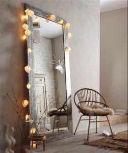 Enmarcado por una guirnalda ligera, este espejo vertical largo de madera envejecida aporta una atmósfera brillante y completa la decoración de inspiración escandinava.