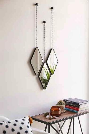 ¡Un toque decorativo súper encantador dado por tres pequeños espejos en forma de diamante suspendidos de cadenas aportan originalidad a la habitación!