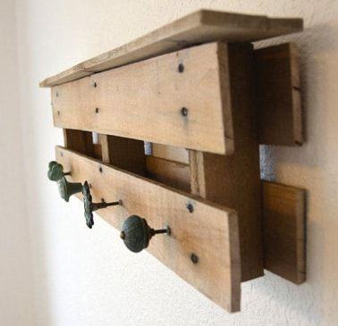 Perchero realizado con un palet de madera cortado por la mitad sobre el que se fijan ganchos de metal o madera según el estilo deseado.