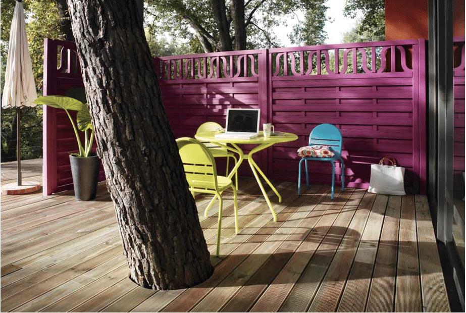 Para crear una terraza en el jardín, un enrejado de madera pintado de color ciruela y muebles de jardín verde y azul.