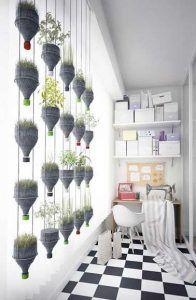 Muro verde realizado con botellas de plástico cortadas y colocado en una estructura metálica.  Florecido con trigo y lentejas, anima la habitación y le da colores.