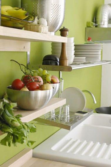 Un hermoso color verde mar en pintura de cocina en el salpicadero y en la parte superior de la pared del fregadero que realza su decoración.  Con estantes de madera pintados de marfil, la distribución de la cocina se optimiza