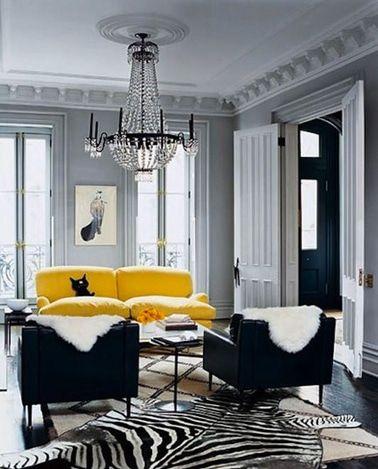 Un sofá de cuero amarillo ilumina la decoración de una sala de estar gris y complementa idealmente los sillones negros