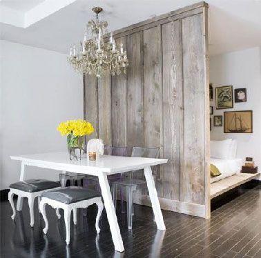 Una idea de la separación de la habitación con tablones de madera grises para separar el área del dormitorio de la sala de estar en un estudio.