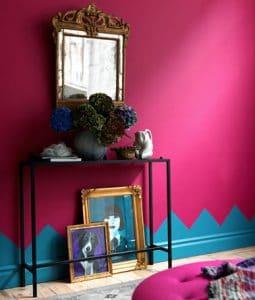 Decoración de salón pequeño con pintura rosa fucsia, zócalos pintados con estampado en la pared en azul vivo.  Consola de hierro negro