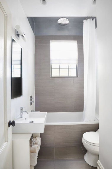 Tranquilo y ultra brillante, este pequeño baño gris está 100% optimizado con su pequeña bañera en la parte trasera de la habitación y una práctica unidad de almacenamiento.