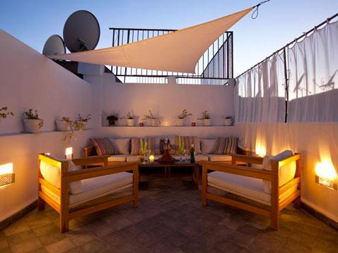 triángulo de lona para sombrilla en una terraza de bricolaje fijada con tensores en las paredes