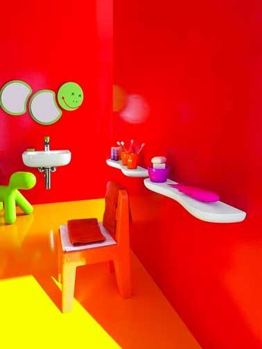 Una decoración de baño en color que aporta a los niños una dosis de buen humor desde el lavado matutino.  Rojo brillante en las paredes, amarillo en el piso y verde lima con un divertido espejo y un perro Fatboy inflable.