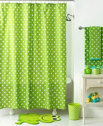 Cortina de ducha y toallas con lunares verdes y blancos, una alfombra de rana verde, un baño infantil elegante y divertido