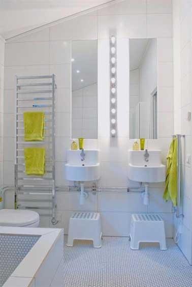 En su baño, a los niños también les gusta encontrar una decoración refinada como la de sus padres.  Azulejos y lavabos blancos, espejos y un toallero de escalera de acero inoxidable con toallas amarillas para un toque de color.
