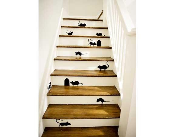 Los patrones de ratones negros en pegatinas colocadas en los escalones blancos del mostrador de la escalera de madera animan el pasillo con humor.  Una decoración de escalera barata.