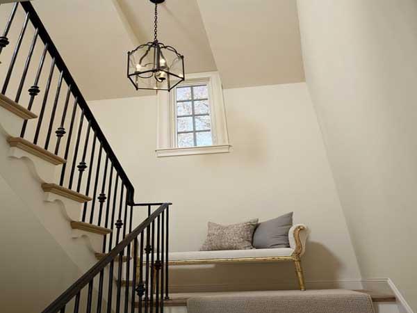 El rellano de una escalera blanca se sublima con un banco retro.  Una instalación en armonía con las paredes pintadas de color crema y la barandilla de la escalera de hierro negro.