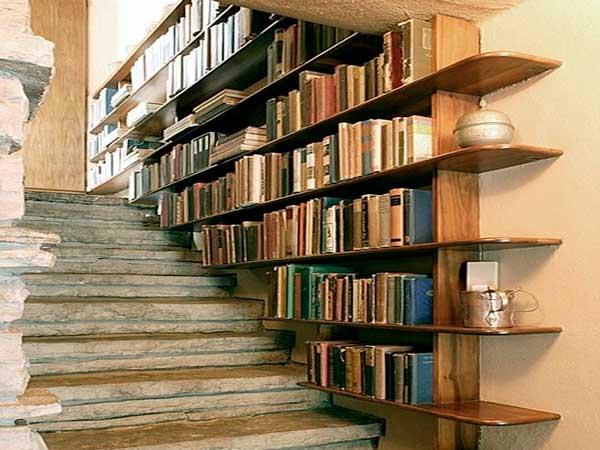 Los espacios de almacenamiento hechos a medida tienen lugar en una pared de la escalera.  De madera barnizada, los estantes combinan con los escalones de piedra.