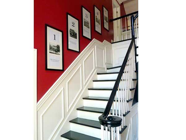 Escalera blanca de estilo contemporáneo con pintura roja brillante en las paredes.  Marcos de fotos de madera, pasamanos y escalones pintados en negro, agregan un toque gráfico