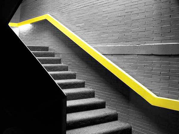 La escalera pintada de gris marengo está grabada con un pasamanos de color amarillo fluorescente.  Perfecto para estructurar las líneas de la escalera y darle luminosidad