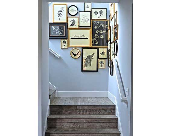 Una escalera pintada en color azul pastel ilumina las escaleras de madera en bruto.  La acumulación de marcos de fotos moteados redondos y cuadrados lo convierte en una decoración recuperada atípica