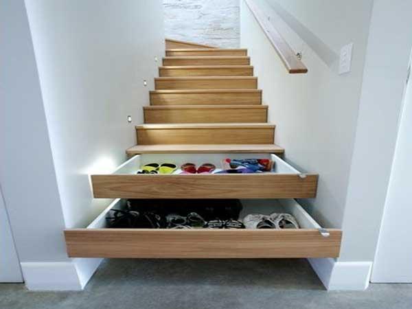 Los cajones de almacenamiento están dispuestos en los escalones de la escalera de madera.  Un consejo que ahorra espacio para espacios pequeños.  Aquí con paredes pintadas de blanco