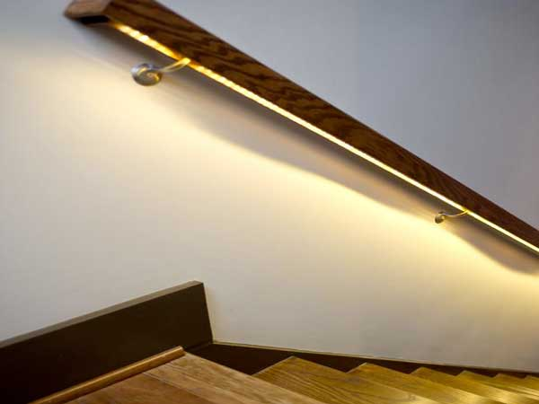 La iluminación LED colocada debajo del pasamanos de la escalera da luz a las escaleras de madera y les da una atmósfera suave y tenue.