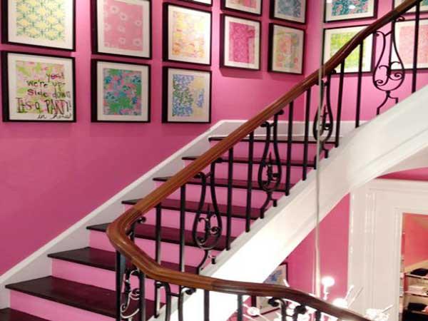 Una pintura rosa moderniza la jaula de esta escalera de madera.  Recordatorio colorido en los escalones traseros y con las tablas de los marcos de fotos alineados horizontalmente