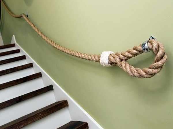 Decoración de escalera barata con una cuerda de marinero como barandilla de escalera.  Asociado con una pintura verde en las paredes y blanca en los escalones traseros.