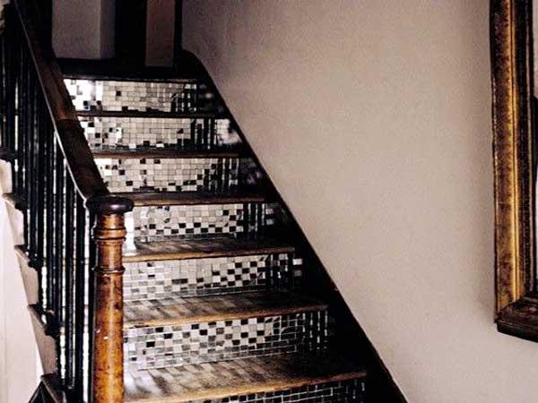 Las baldosas adhesivas de espejo colocadas en los escalones del mostrador de la escalera de madera iluminan una escalera.  Aquí casado con paredes pintadas de color blanquecino