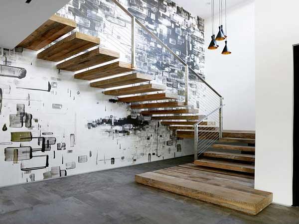 Una pared de arte callejero con vigas de madera y escalones de diseño hacen una decoración urbana de moda para escaleras.  La barandilla de metal y las luces colgantes estilo loft acentúan el efecto