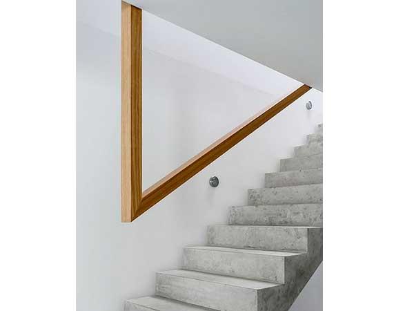 Ultramoderno, el hueco de la escalera con paredes blancas con su barandilla de madera de diseño y escalera de hormigón.  La madera rubia aporta calidez a esta decoración fría