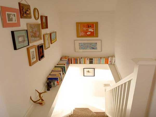 En esta escalera, una viga crea un estante para guardar libros.  Marcos de fotos de todos los tamaños colorean las paredes blancas