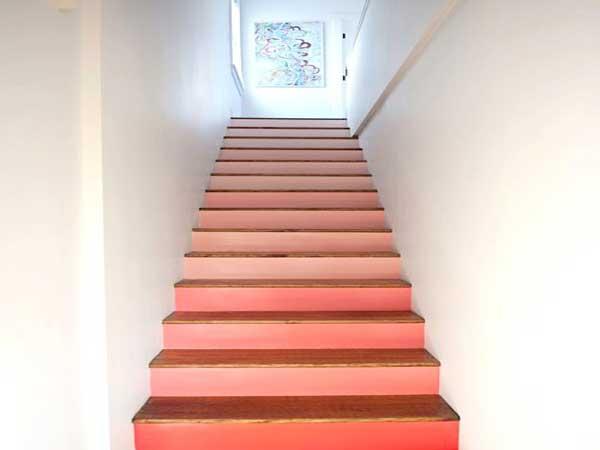 El color rosa salmón de los escalones del mostrador despierta la decoración blanca de esta escalera.  Una idea decorativa para rehacer con una capa de pintura de colores brillantes.