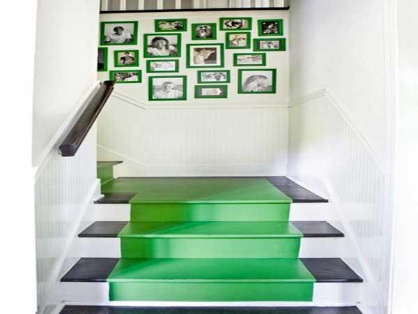 Una alfombra está pintada a lo largo de la escalera con pintura verde.  Mejorado por los escalones negros, coincide con los marcos de fotos verdes.