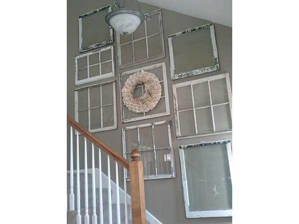 Una escalera sublimada con baldosas de vidrio recuperado repintadas en blanco.  En armonía con las barandillas y el zócalo, se destacan contra la pared gris perla.