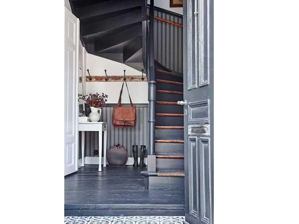 Con su papel pintado a rayas y paredes pintadas de gris antracita, la escalera de caracol aporta carácter a la entrada.  De acuerdo con el parquet repintado