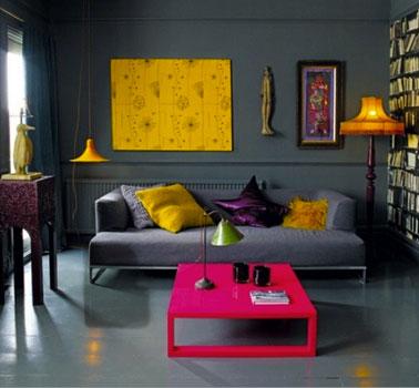 En un salón con paredes de color gris marengo, para aportar luz y dinamismo, una mesa pintada en rosa llamativo, cojín y lona de color amarillo intenso
