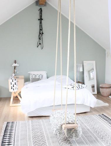 Una decoración muy original en este dormitorio en el ático con un pequeño columpio colgante y una hermosa pared pintada en color pastel para un ambiente delicado