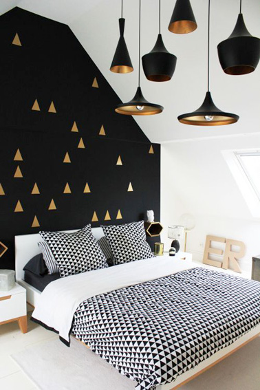 Dorado y negro para este hermoso dormitorio de invitados en el ático.  Una habitación con una decoración original con sus lámparas colgantes y triángulos dorados.