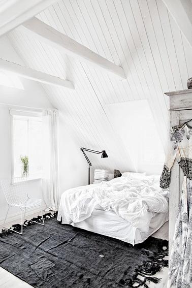 Un pequeño espacio ideal para relajarse y descansar, nos encanta esta habitación en el ático con decoración totalmente blanca y alfombra gris antracita.