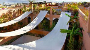 Brise-soleil realizado con tiras de lona blanca en una terraza de estilo mediterráneo