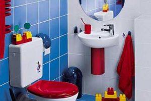Colores decorativos ideales para un baño divertido para niños pequeños.  Inspirado en los colores del Légo, un alicatado azul y blanco en la pared y el suelo, el asiento del inodoro y los artículos de tocador de color rojo vivo alrededor de los elementos sanitarios ajustados a su tamaño.
