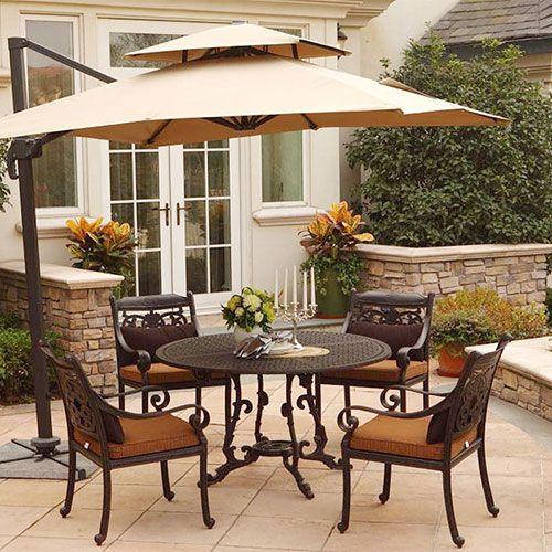 Sombrilla grande en jardín con mesa y sillas