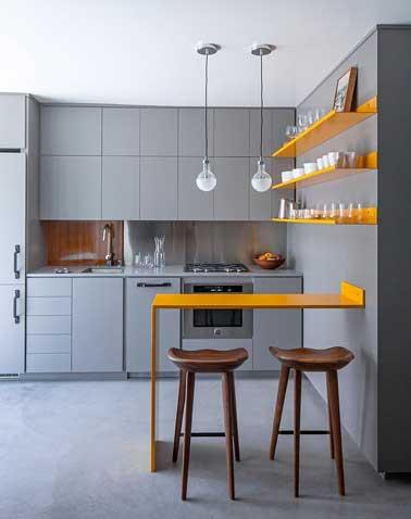 Con el gris, la pequeña cocina adquiere profundidad.  El color naranja brillante de los estantes y la esquina de la mesa le da ritmo a la decoración y le da tono a la habitación