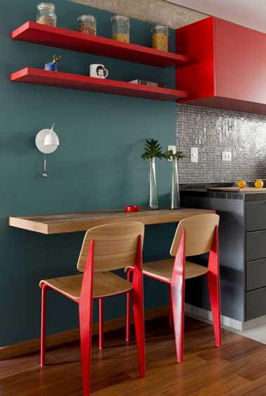 La pintura roja de la cocina gris marca el estilo urbano de esta pequeña estancia.  La madera elige en las sillas, la mesa y el suelo de parquet delimitan el espacio