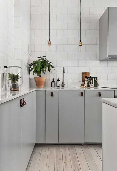 Blanco y gris, un dúo de colores atemporal en esta cocina decorativa gris.  Gabinete gris, pared de azulejos de metro blanco, piso de madera blanqueada y detalle de cuero